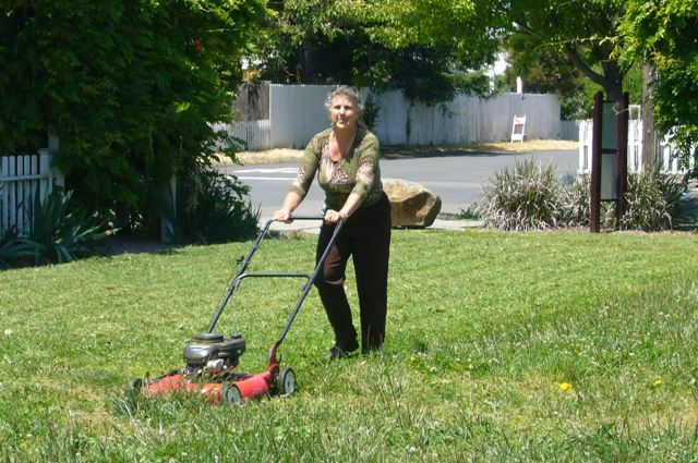 Dr. Deb mows the grass at DeMeo